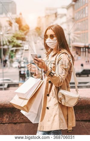Beautiful Young Girl Shopaholic In Medical Face Mask And Sunglasses Use Smart Phone While Shopping I