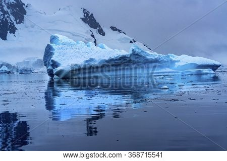 Floating Blue Iceberg Reflection Snow Mountains Paradise Bay Skintorp Cove Antarctica. Glacier Ice B