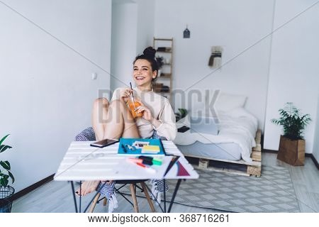 Cheerful Woman Drinking Juice While Sitting At Desk At Home