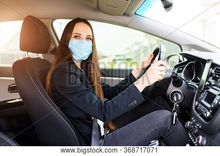 Young Woman With Surgery Protective Mask On Her Face Is Driving Car. Virus Protection, Keep Yourself
