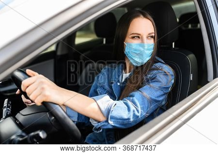 Protective Measures In A Car During Pandemia, Epidemia. A Young Woman In Medical Mask Is Driving A C