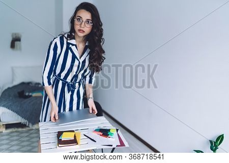 Ambitious Smart Woman In Pleasant Outfit Resting Laptop Against Worktop