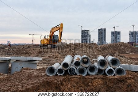 Excavator In Action At Construction On Earthwork. Laying Concrete Drainage Pipes Of Underground Stor