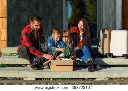 Satisfied Young Parents With Their Happy Children Sitting On New Houses Stairs And Get From The Cart