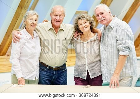 Group of seniors retired as friends in retirement home smiling happily