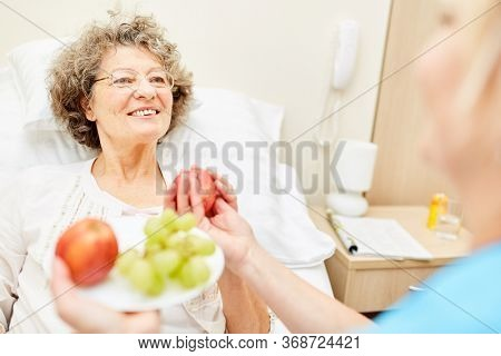 Sick senior woman gets fresh fruit from a nursing assistant in the elderly care