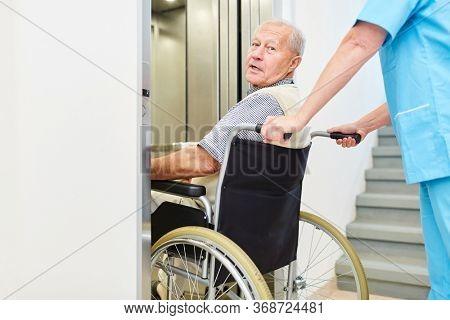 Nursing a senior man in a wheelchair in a nursing home or nursing home