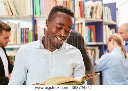 Young African student or migrants reading a book in a library or bookstore