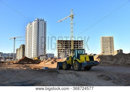 Front-end Loader And Excavator On Road Work. Tower Crane In Action At Construction Site. Earth-movin