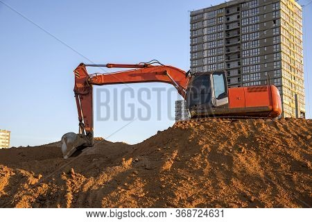 Excavator Working At Construction Site. Backhoe During Earthworks. Digging Ground For The Foundation
