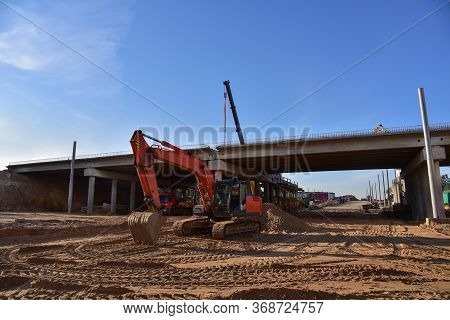 Excavator Working At Construction Highway Ramps And Bridgeworks. Roundabout And Traffic Bridge Const