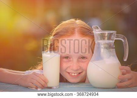 Healthy Baby Milk - Portrait Of A Beautiful Redhead Girl Drinking Fresh Milk Outdoors. Milk Is Fresh