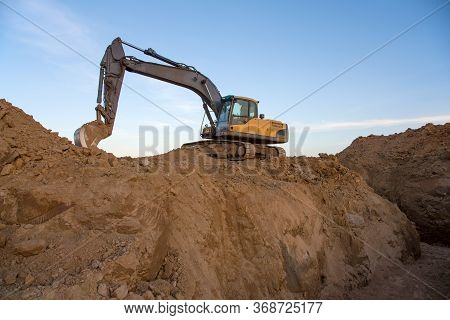 Excavator Working At Construction Site On Earthworks. Backhoe Digs Ground In Pit For Laying Concrete