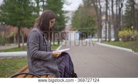 Woman Reading A Book On A Park Bench, Leisure Time In Autumn Park. Fashion Woman In Yellow Coat Sitt