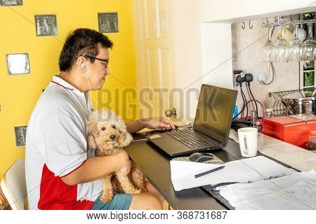 Matured Asian Business Man Work From Home Accompanied By Pet Dog During Lockdown.