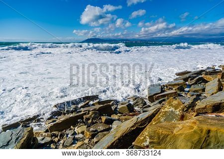 Storm In Tsemesskaya Bay. Turquoise Waves With Beautiful Snow-white Foam Fall On Cape Doob. There Ar
