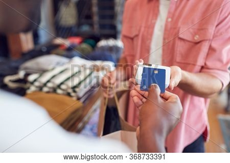 Man In Clothing Store Making Contactless Payment At Sales Desk Holding Credit Card To Reader