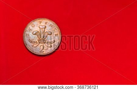 British Coin 2 Pence (2001) Isolated On Red Background With Blurry And Space For Copy Text. Front Si
