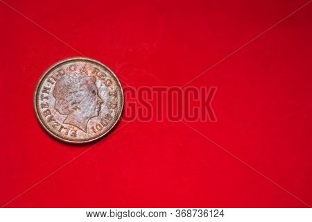 British Coin 2 Pence (2001) Isolated On Red Background With Blurry And Space For Copy Text. Back Sid