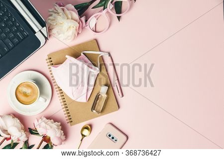 Home office table desk, Flat lay blogger workspace mockup with coffee, computer, flowers, face mask, sanitizer and feminine accessories on pink background.