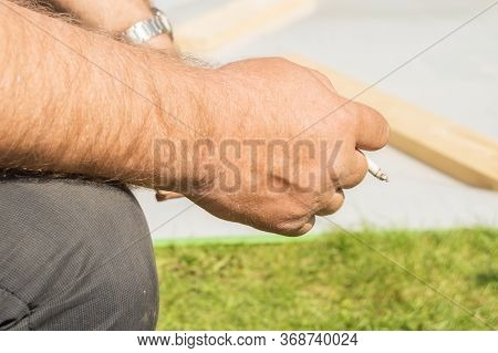 Close-up Of An Elderly Mans Hand Holding A Cigarette And Smoking Against An Open Nature Bokeh. Conce