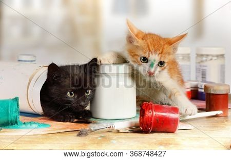 Two Mischievous Kittens Played Pranks On The Artist's Table Spilling A Can Of Paint