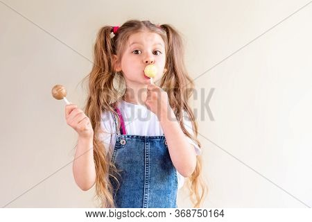 A Little Girl With Ponytails Is Licking A Lollipop And Holding A Second Lollipop In Her Hand.