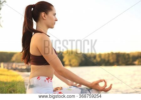 Young Pretty Woman In Lotus Pose In Green Park.