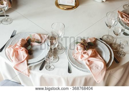 Close Up Festive Table Setting With Empty Wine Glasses And Two Plates