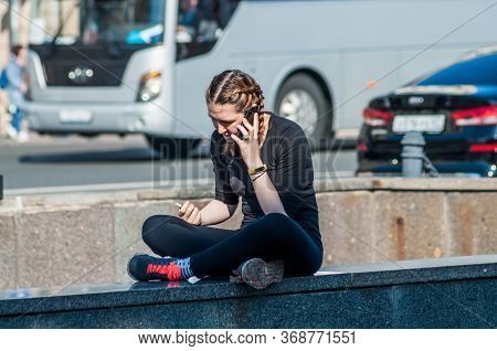 Saint Petersburg, Russia - 22 Augusr 2019. Girl Talks On The Phone Sitting On A Narrow Parapet In A