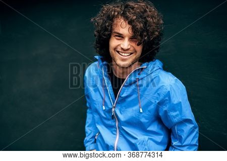 Closeup Outdoor Image Of Smiling Young Man With Curly Hair Sitting On Stairs Of A Building With A Ba