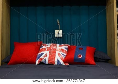 Three Red Pillows Lie On The Bed. Grey Duvet. Blue Wooden Wall. The Lamp On The Wall. The Design Of