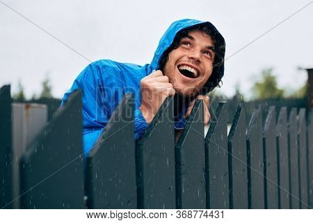 Happy Man Smiling Broadly And Wearing Blue Raincoat During Rain Outside. Handsome Male In Blue Rainc