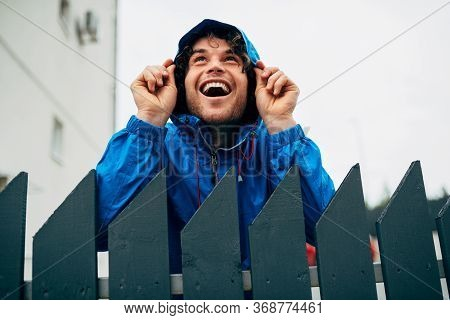 Outdoor Image Of Happy Man Smiling Broadly And Wearing Blue Raincoat During Rain. Handsome Male In B
