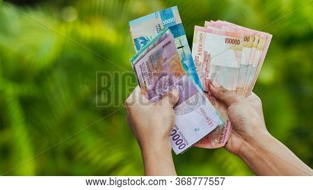 The Girl Recounts In The Hands Of Indonesian Money. Indonesian Rupee.