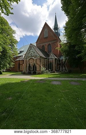 Part Of The Luebeck Cathedral With Narthex And Ridge Turret, View From The Idyllic Churchyard With