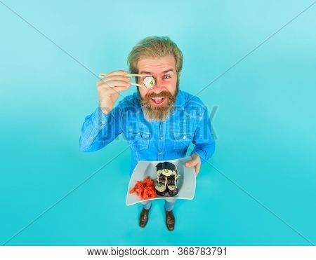 Exotic Nutrition. Seafood. Man Eating Sushi. Man Hold Piece Sushiroll In Front Of Eye. Man With Sush