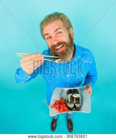 Sushi Delivery. Chopsticks Holding Sushi Roll. Bearded Man With Sushi. Japan. Hipster Eating Sushi R