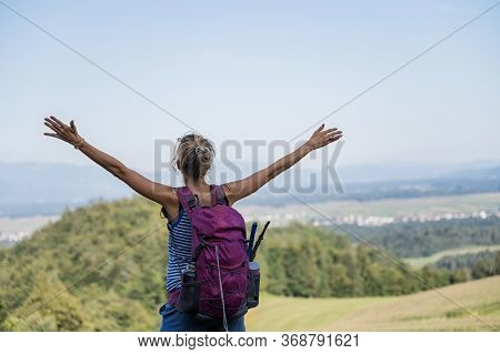 View From Behind Of A Young Female Hiker With Purple Backpack On Her Back, Standing And Looking At B