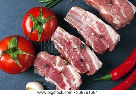 Raw Slices Of Pork On A Black Slate Board, Tomatoes, Red Pepper And Powder. Pork Belly With Vegetabl