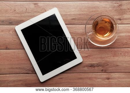 Top View Of Digital Tablet And Tea On Wooden Table