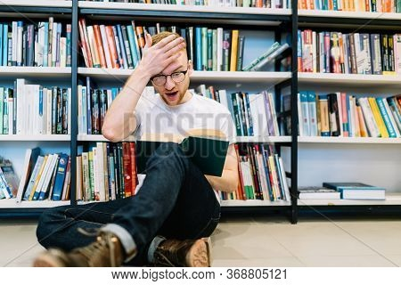 Shocked Man Reading Book And Touching Forehead On Floor Near Bookshelf