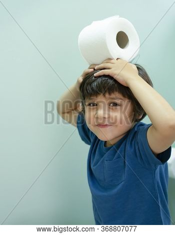 Active Child Sitting In The Toilet Playing With Toilet Paper, Cropped Shot Kid Boy Sitting In The Re