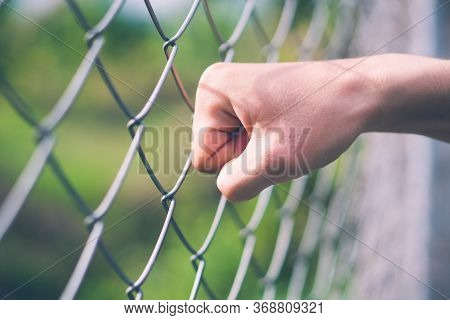 Hand Punch Hit At Wire Mesh Fence, Freedom And Imprison Concept