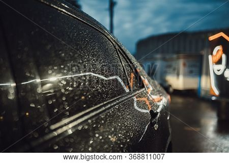Drops Of Water On The Car After Rain. Raindrops On A Black Car Glare Or Reflect From Night Lights La
