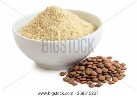 Dried Lentil Flour In A White Ceramic Bowl Next To A Pile Of Brown Lentils Isolated On White.