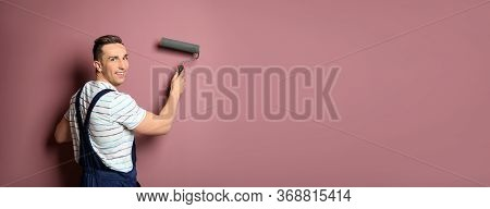 Professional Decorator With Paint Roller Near Pink Wall, Space For Text. Banner Design