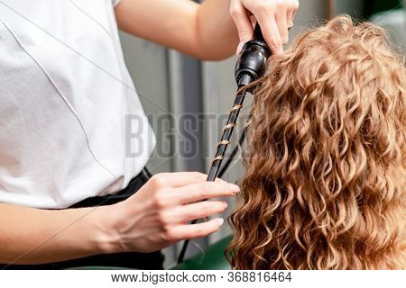 Hairdresser Hands Curl Womans Hair By Curling Iron In Salon.