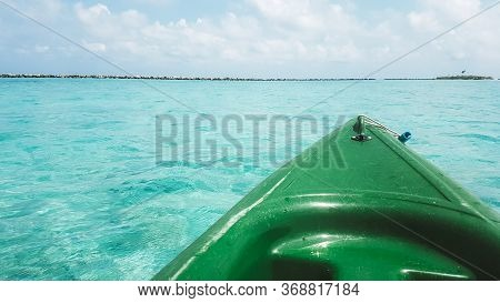 Close Up View Of Green Canoe Nose Surrounded By Clystal Clear Tortoise Water. Sunny Day At Maldives