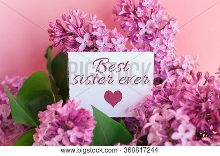 Inscription Best Sister Ever On A White Gift Card In A Beautiful Spring Bouquet Of Lilac Flowers